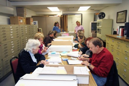 Volunteers matching records for ballots received against those distributed
